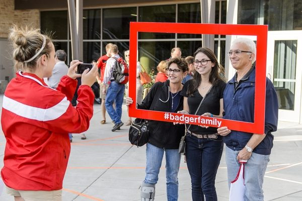 A UW student and their two family members take a picture with a photo frame labeled