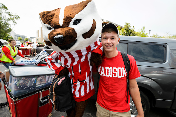 UW-Madison student standing next to Bucky Badger
