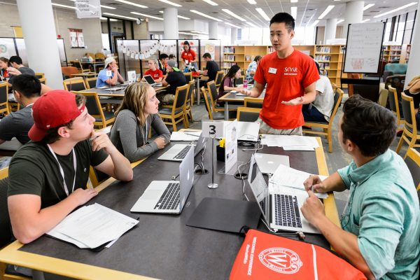 A SOAR Peer Advisor meets with incoming first-year undergraduates and helps them to register for their classes using laptop computers at SOAR.