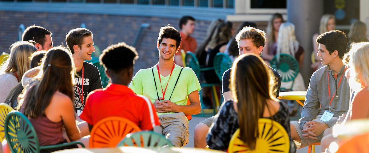 Incoming first-year undergraduates talk about the challenges new students may face as they transition to campus life as a new-student leader facilitates a small-group discussion.