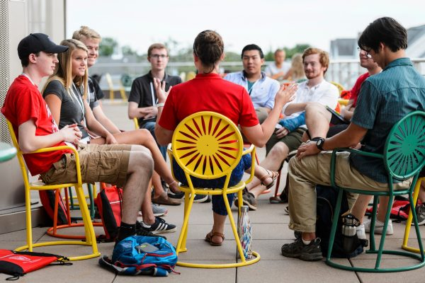 At center, a new-student leader talks with incoming first-year undergraduates and facilitates a small-group discussion at SOAR.