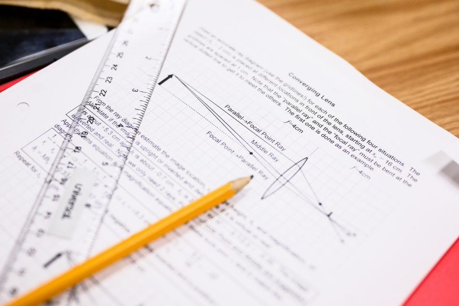 A pencil is laying on top of a UW math course exam paper packet.