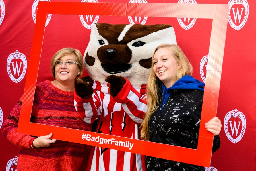 Mother and daughter with Bucky Badger and a frame that says #Badgerfamily