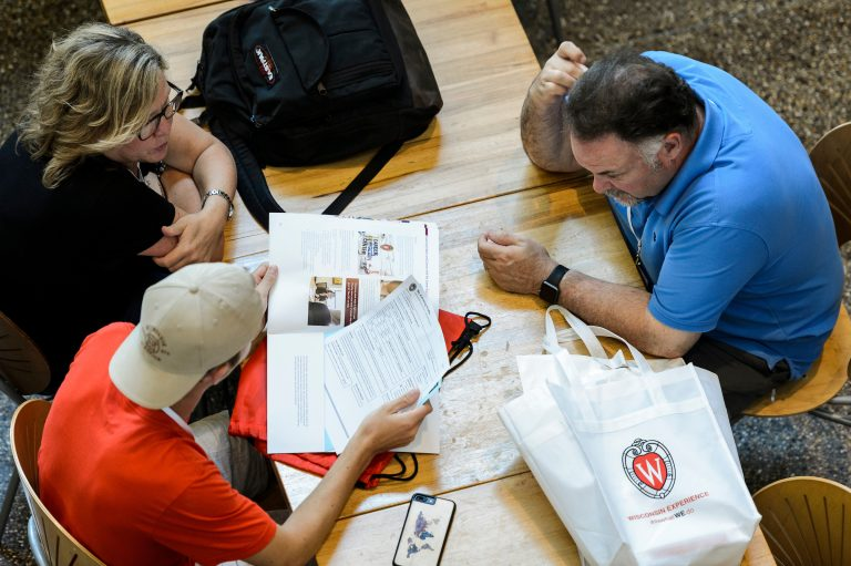 A family looks over materials during a break in Student Orientation, Advising and Registration (SOAR) session