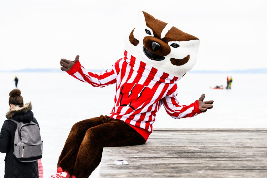 Bucky Badger sitting at Memorial Union Terrace with frozen Lake Mendota in background