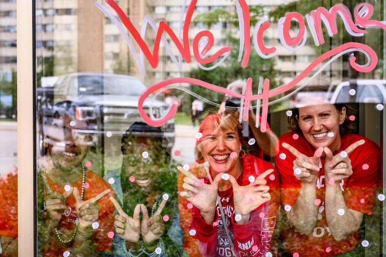 """UW-Madison staff smiling behind a window that has """"Welcome"""" pained on it"""
